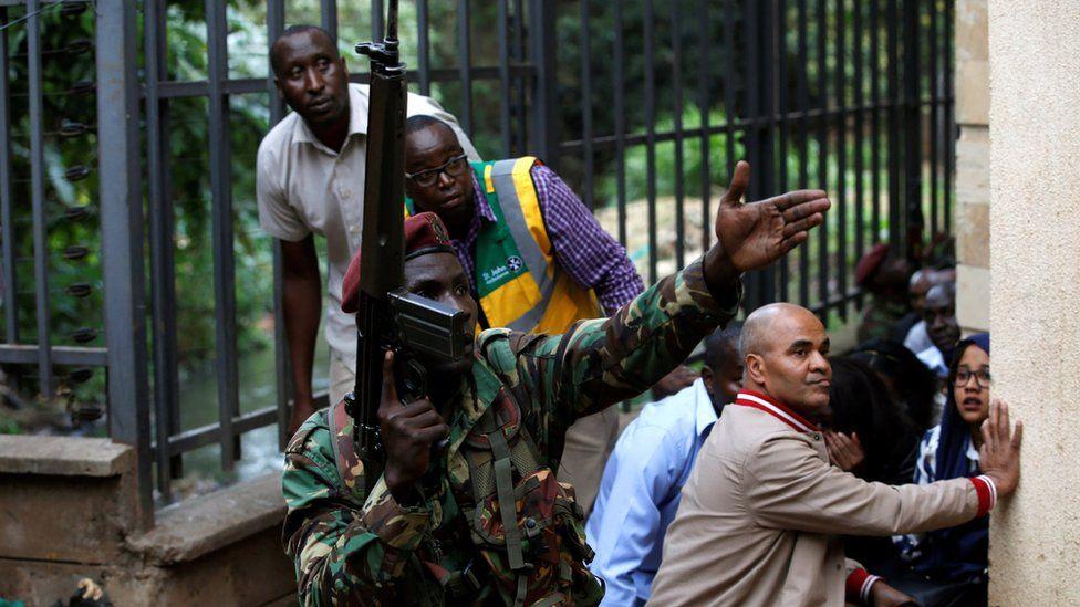 Kenyan security operative guiding civilians