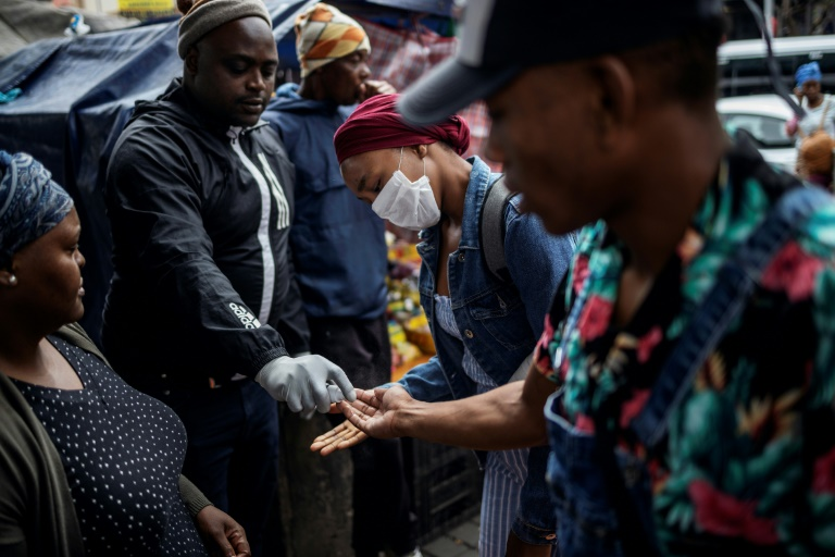 African man sharing sanitizer with others